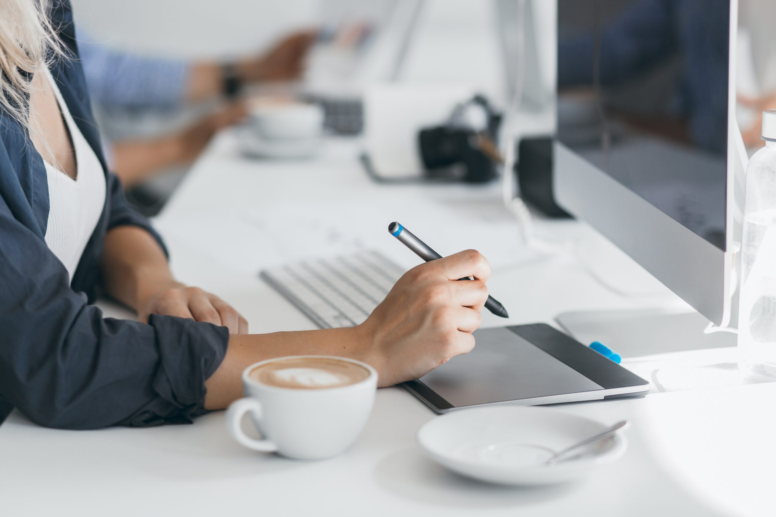 Portrait of freelance web-designer drinking coffee at workplace and holding stylus. Lightly-tanned lady in black shirt using tablet in her office, sitting in front of computer..